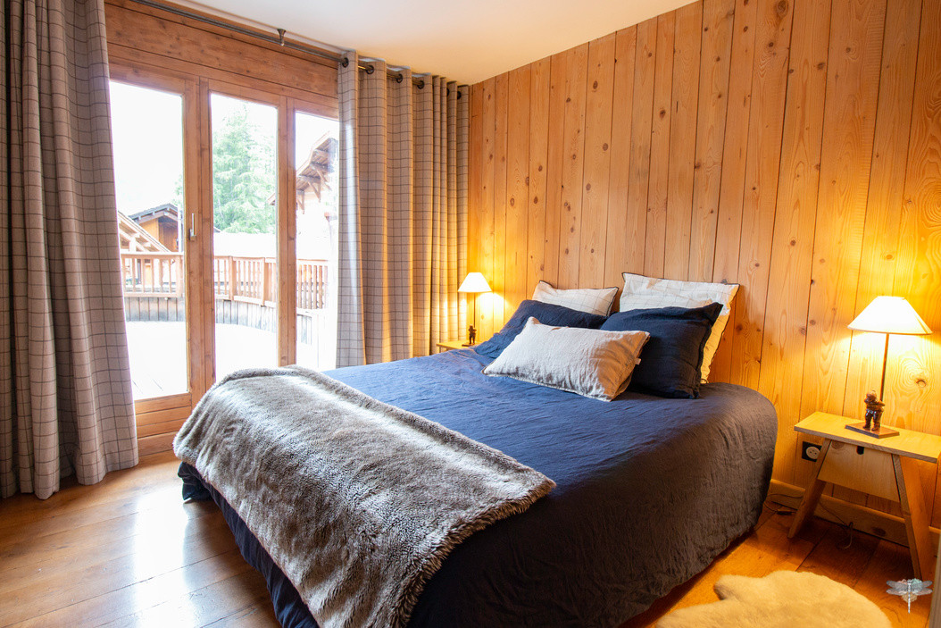 Décoration d'un chalet de montagne à Val d'Isère, par Carnets Libellule. Coralie Vasseur est votre architecte d'intérieur UFDI en Savoie et sur toute la France : vue d'ensemble sur la chambre parentale et sa vue sur l'immense balcon. Tête de lit en bois massif et linge de lit en lin lavé