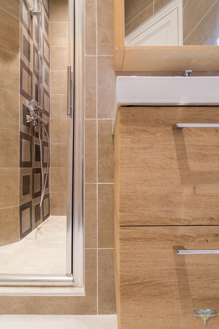 Rénovation et décoration d'une salle d'eau aux couleurs naturelles à Paris par Carnets Libellule. Coralie Vasseur est votre Décoratrice d'intérieur UFDI à Compiegne : faïence de la douche géométrique et meuble vasque en bois