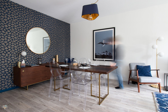 Décoration d'une pièce de vie chic et poétique à Compiègne par Carnets Libellule. Coralie Vasseur est votre Décoratrice d'intérieur UFDI dans l'Oise : Vue d'ensemble sur la salle à manger et ses meubles en bois foncé, papier peint art déco bleu et doré