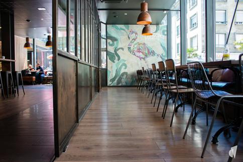 Aménagement et décoration d'un bar restaurant industriel jungle à Compiègne, par l'agence Coralie Vasseur. Coralie Vasseur est votre architecte d'intérieur et décoratrice UFDI à Annecy, Genève et en Haute Savoie : grande verrière sur mesure et papier peint panoramique fantaisie