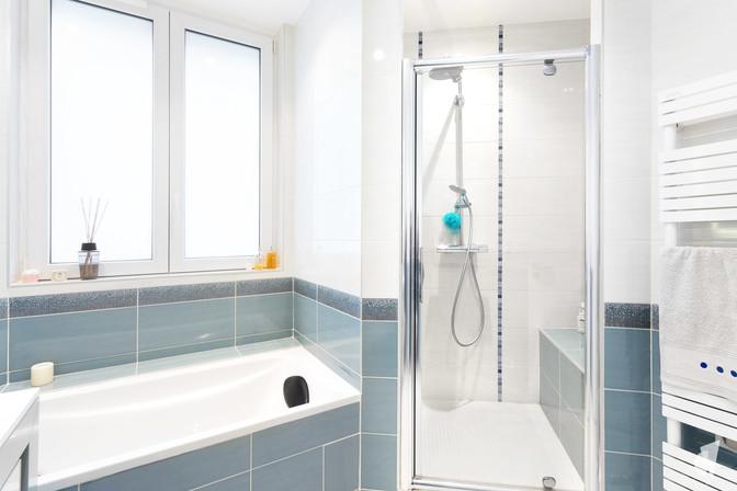 Création d'une salle de bains dans un appartement à Annecy, par le Studio Coralie Vasseur. Coralie Vasseur est votre architecte d'intérieur et décoratrice UFDI à Annecy, Genève et en Haute Savoie : vue d'ensemble sur la pièce d'eau avec baignoire et douche, ambiance lumineuse dans les tons bleus glaciers