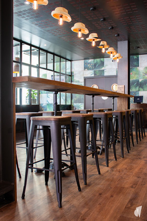 Aménagement et décoration d'un bar restaurant industriel jungle à Compiègne, par l'agence Coralie Vasseur. Coralie Vasseur est votre architecte d'intérieur et décoratrice UFDI à Annecy, Genève et en Haute Savoie : grande table d'hôtes en bois massif et suspensions chapeaux de paille