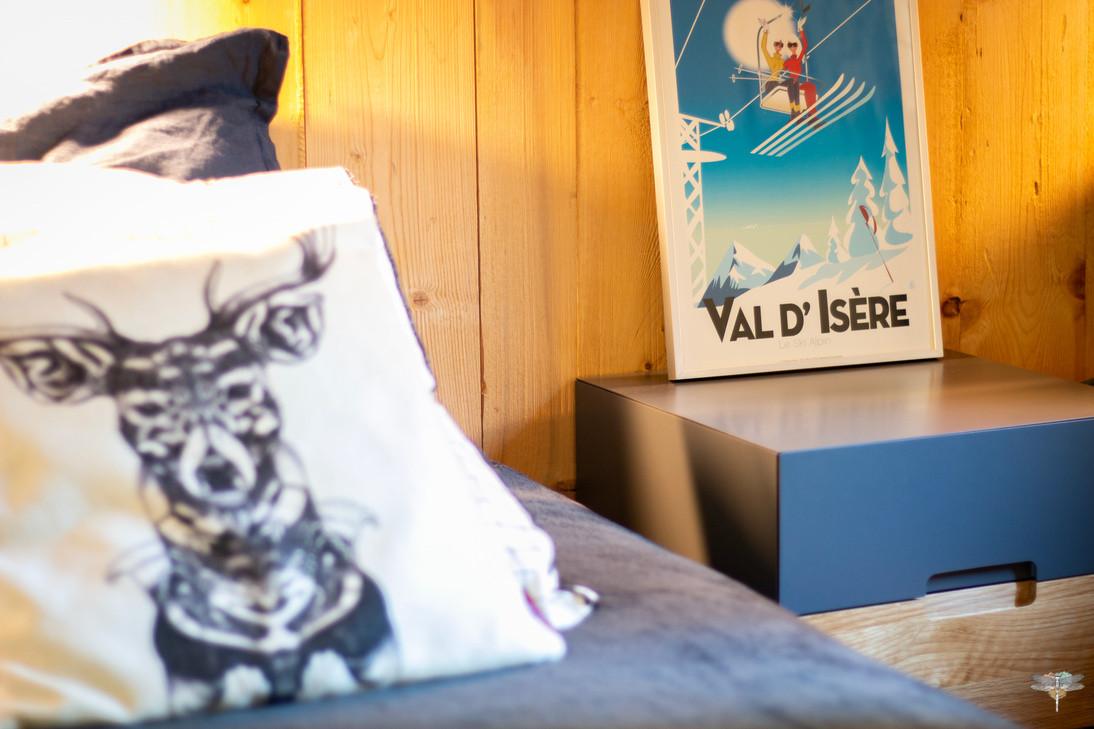 Décoration d'un chalet de montagne à Val d'Isère, par Carnets Libellule. Coralie Vasseur est votre architecte d'intérieur UFDI en Savoie et sur toute la France : zoom sur l'affiche Val d'Isère et le coussin cerf