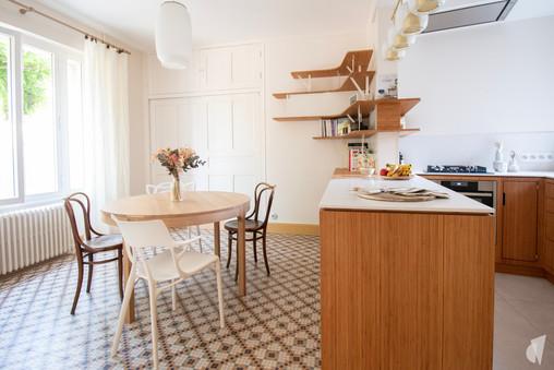 Création d'une cuisine au design sur-mesure à Annecy, par le Studio Coralie Vasseur. Coralie Vasseur est votre architecte d'intérieur et décoratrice UFDI à Annecy, Megève et en Haute Savoie : cuisine ouverte sur salle à manger avec étagères suspendues