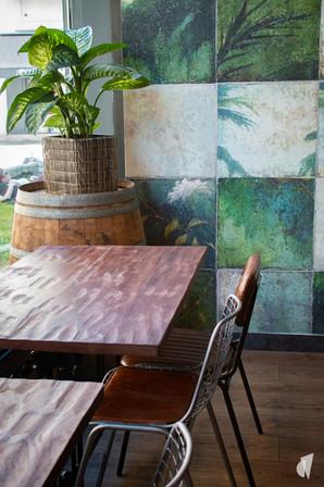 Aménagement et décoration d'un bar restaurant industriel jungle à Compiègne, par l'agence Coralie Vasseur. Coralie Vasseur est votre architecte d'intérieur et décoratrice UFDI à Annecy, Genève et en Haute Savoie : tables en bois massif et papier peint panoramique