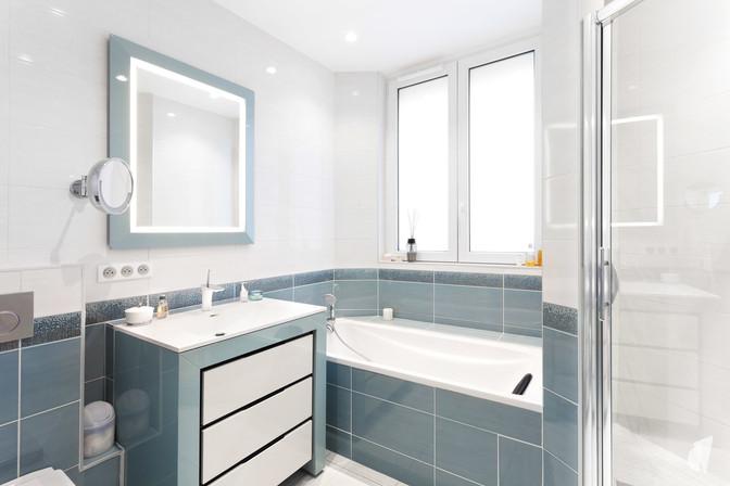 Création d'une salle de bains dans un appartement à Annecy, par le Studio Coralie Vasseur. Coralie Vasseur est votre architecte d'intérieur et décoratrice UFDI à Annecy, Genève et en Haute Savoie : vue d'ensemble sur la pièce d'eau avec douche, baignoire et meuble vasque couleur bleu glacier