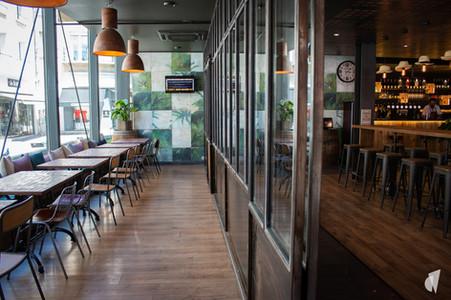 Aménagement et décoration d'un bar restaurant industriel jungle à Compiègne, par l'agence Coralie Vasseur. Coralie Vasseur est votre architecte d'intérieur et décoratrice UFDI à Annecy, Genève et en Haute Savoie : verrière sur-mesure et espace privatisable, papier peint jungle panoramique