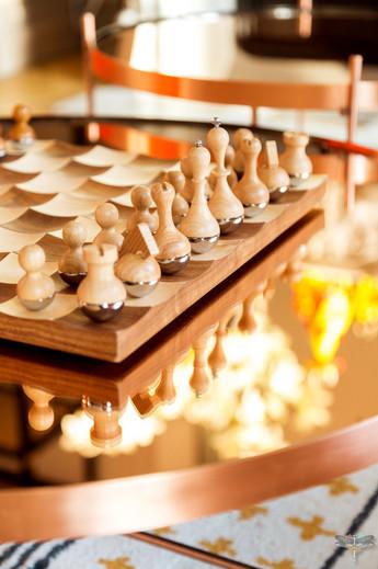 Décoration d'un double salon moderne dans un appartement Haussmannien à Paris 17 par Carnets Libellule. Coralie Vasseur est votre Décoratrice d'intérieur UFDI à Compiegne : jeu d'échec en bois élégant, design et table basse cuivrée
