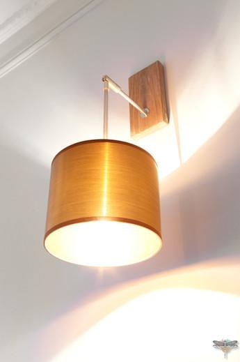 Décoration d'un double salon moderne dans un appartement Haussmannien à Paris 17 par Carnets Libellule. Coralie Vasseur est votre Décoratrice d'intérieur UFDI à Compiegne : applique murale avec abat-jour cuivré, luminaire sur mesure
