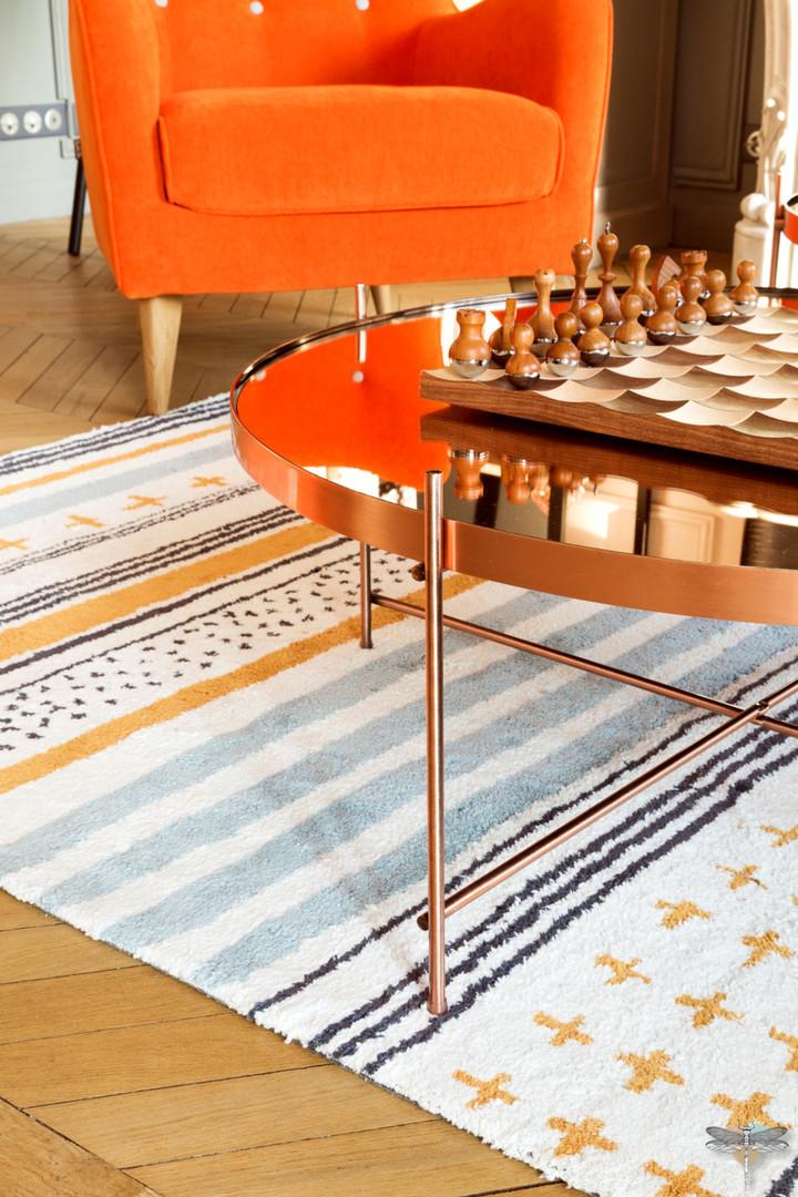Décoration d'un double salon moderne dans un appartement Haussmannien à Paris 17 par Carnets Libellule. Coralie Vasseur est votre Décoratrice d'intérieur UFDI à Compiegne : table basse ronde cuivrée et tapis toulemonde bochart