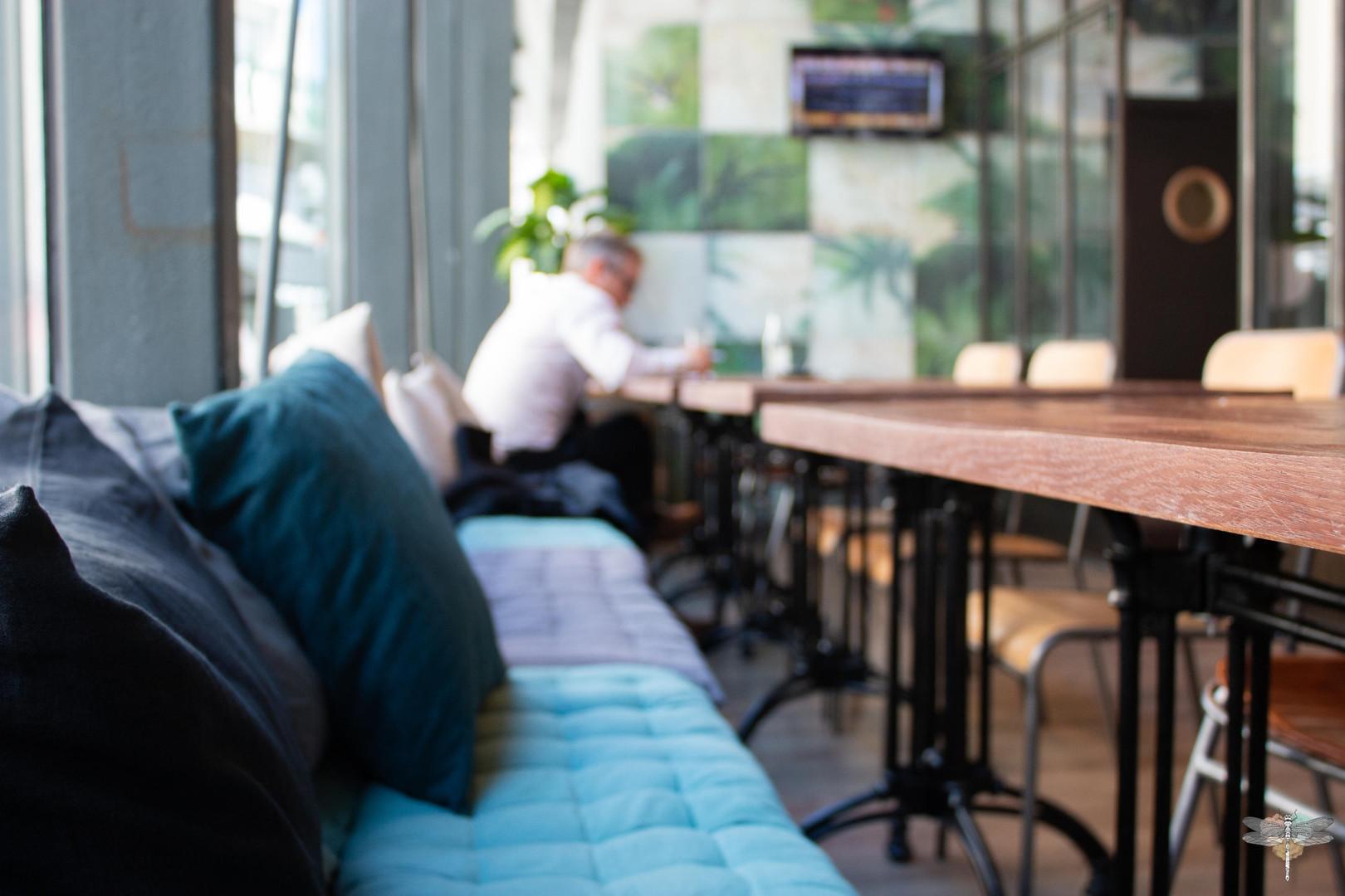 Agencement et décoration du restaurant industriel voyage EAP's CAFE par Carnets Libellule. Coralie Vasseur est votre Décoratrice d'intérieur UFDI à Compiegne : banquettes cosy avec coussins