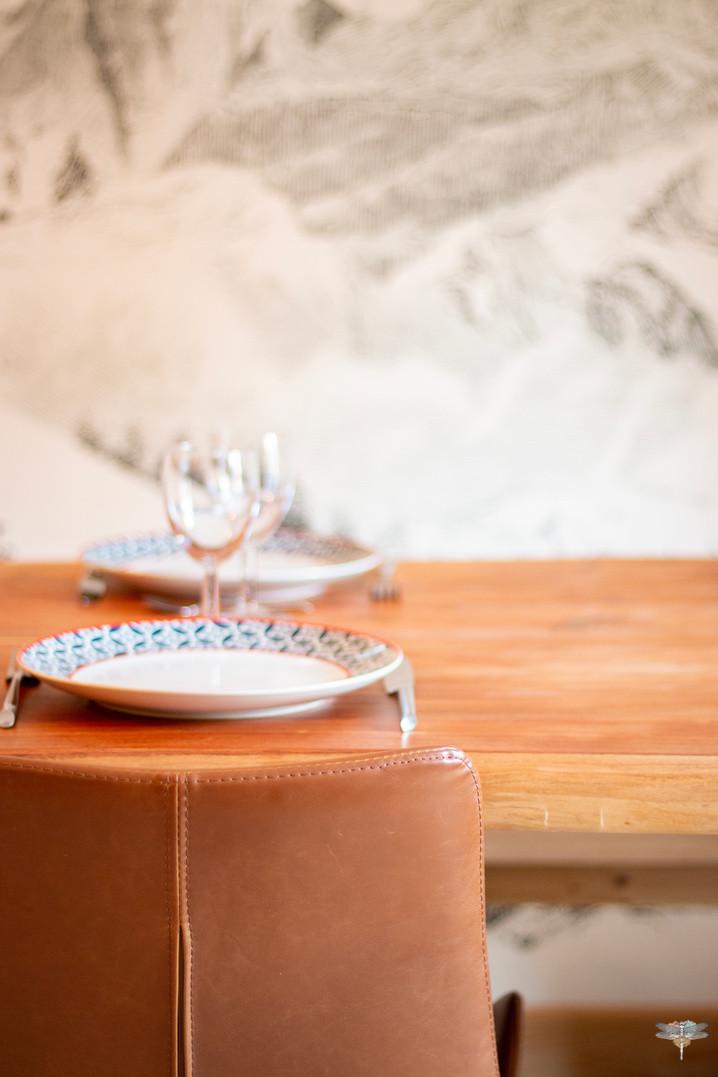 Décoration d'un chalet de montagne à Val d'Isère, par Carnets Libellule. Coralie Vasseur est votre architecte d'intérieur UFDI en Savoie et sur toute la France : détail sur une chaise en cuir et la table en bois massif