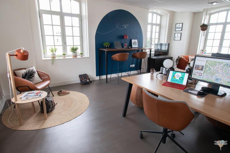 Aménagement et décoration d'un espace de bureaux professionnels à Senlis, pour DecoWorkers, par Carnets Libellule. Coralie Vasseur est votre architecte d'intérieur UFDI à Compiegne : vue globale de l'espace principal avec arche bleue color zoning, plan de travail assis debout, espace accueil et lecture