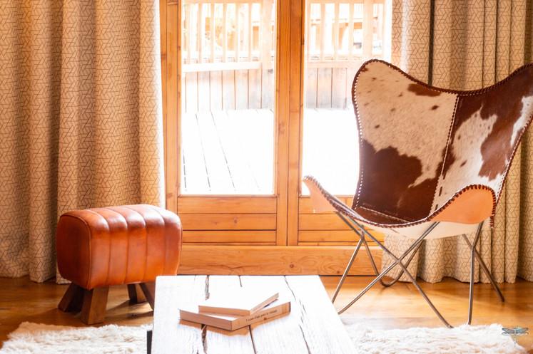 Décoration d'un chalet de montagne à Val d'Isère, par Carnets Libellule. Coralie Vasseur est votre architecte d'intérieur UFDI en Savoie et sur toute la France : lumière naturelle baignant le salon, fauteuil papillon en peau de vache et pouf en cuir, table basse en bois massif