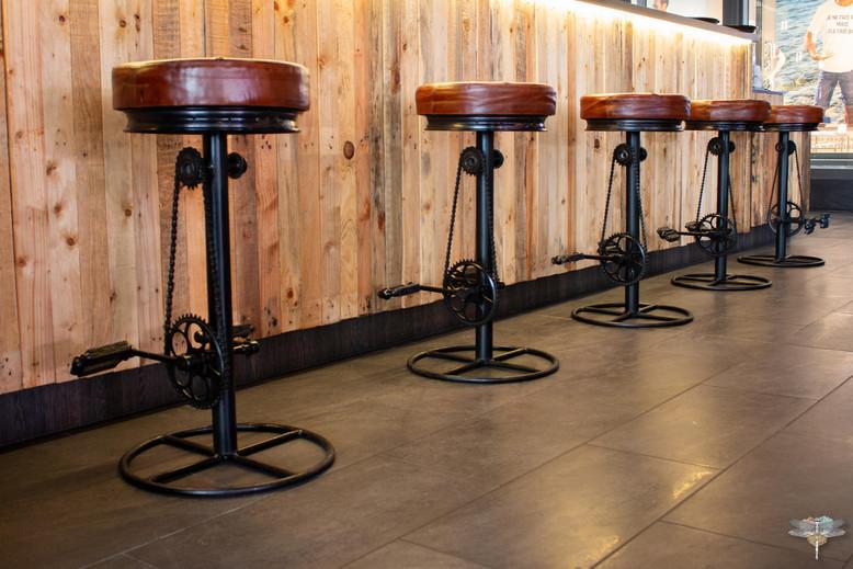 Agencement et décoration du restaurant industriel voyage EAP's CAFE par Carnets Libellule. Coralie Vasseur est votre Décoratrice d'intérieur UFDI à Compiegne : tabourets pédalier métal et cuir industriel