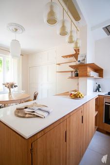 Création d'une cuisine au design sur-mesure à Annecy, par le Studio Coralie Vasseur. Coralie Vasseur est votre architecte d'intérieur et décoratrice UFDI à Annecy, Megève et en Haute Savoie : ilot central de cuisine en bambou et quartz avec suspensions en laiton