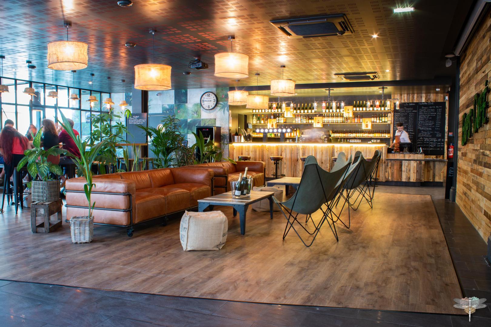 Agencement et décoration du restaurant industriel voyage EAP's CAFE par Carnets Libellule. Coralie Vasseur est votre Décoratrice d'intérieur UFDI à Compiegne : vue d'ensemble de l'espace lounge et bar avec canapés cosy en cuir