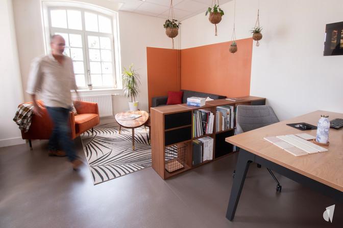 Aménagement et décoration des bureaux d'une startup à Senlis, par l'agence Coralie Vasseur. Coralie Vasseur est votre architecte d'intérieur et décoratrice UFDI à Annecy, Genève et en Haute Savoie : espace salon séparé par une bibliothèque, color zoning orange