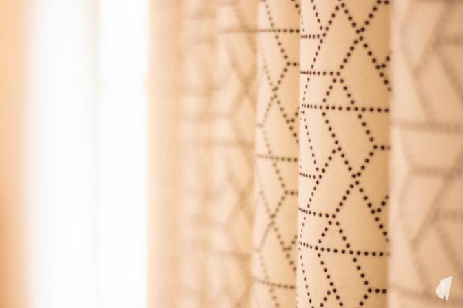 Aménagement et décoration d'une agence de construction de maisons à Compiègne, par l'agence Coralie Vasseur. Coralie Vasseur est votre architecte d'intérieur et décoratrice UFDI à Annecy, Genève et en Haute Savoie : détail sur le tissu des rideaux sur mesure, confection haut de gamme