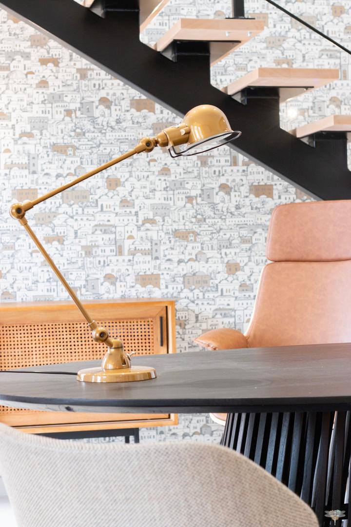 Décoration des bureaux d'une agence de construction de maisons à Compiègne, par Carnets Libellule. Coralie Vasseur est votre architecte d'intérieur UFDI à Compiègne, Annecy et sur toute la France : lampe de bureau couleur or et fauteuil en cuir