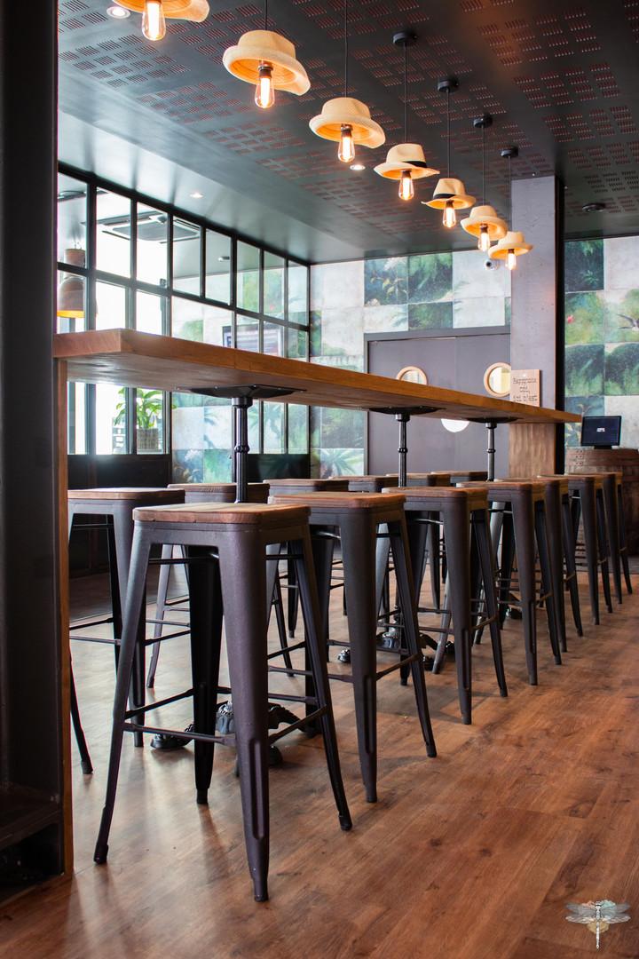 Agencement et décoration du restaurant industriel voyage EAP's CAFE par Carnets Libellule. Coralie Vasseur est votre Décoratrice d'intérieur UFDI à Compiegne : table d'hôte et tabourets métal