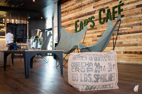 Aménagement et décoration d'un bar restaurant industriel jungle à Compiègne, par l'agence Coralie Vasseur. Coralie Vasseur est votre architecte d'intérieur et décoratrice UFDI à Annecy, Genève et en Haute Savoie : pouf en sac de jute recyclé et logo végétal stabilisé