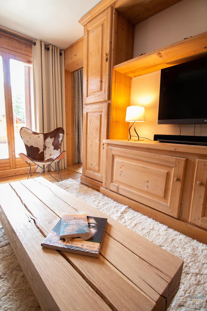 Décoration d'un chalet de montagne à Val d'Isère, par Carnets Libellule. Coralie Vasseur est votre architecte d'intérieur UFDI en Savoie et sur toute la France : zoom sur le salon et son agencement en bois sur-mesure, table basse en bois massif