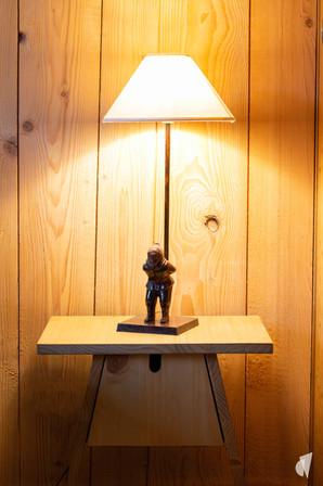Décoration d'un chalet haut de gamme à Val d'Isère, par l'agence Coralie Vasseur. Coralie Vasseur est votre architecte d'intérieur et décoratrice UFDI à Annecy, Genève et en Haute Savoie : zoom sur la lampe skieur en métal et la table de chevet en forme de nichoir
