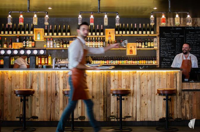 Aménagement et décoration d'un bar restaurant industriel jungle à Compiègne, par l'agence Coralie Vasseur. Coralie Vasseur est votre architecte d'intérieur et décoratrice UFDI à Annecy, Genève et en Haute Savoie : bar branché en bois recyclé et tabourets pédaliers