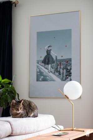 Aménagement et décoration d'une d'une pièce de vie à l'ambiance chic et poétique à Annecy, par l'agence Coralie Vasseur. Coralie Vasseur est votre architecte d'intérieur et décoratrice UFDI à Annecy, Genève et en Haute Savoie : zoom sur la lampe de designer en laiton et verre de chez Flos, cadre à bord laiton et image poétique