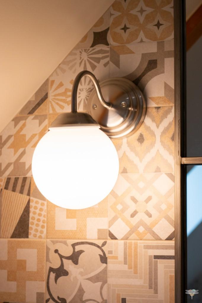 Agencement et décoration d'une salle de bains par Carnets Libellule. Coralie Vasseur est votre Décoratrice d'intérieur UFDI à Compiegne : Zoom sur l'applique murale rétro vintage assortie au miroir et à la robinetterie