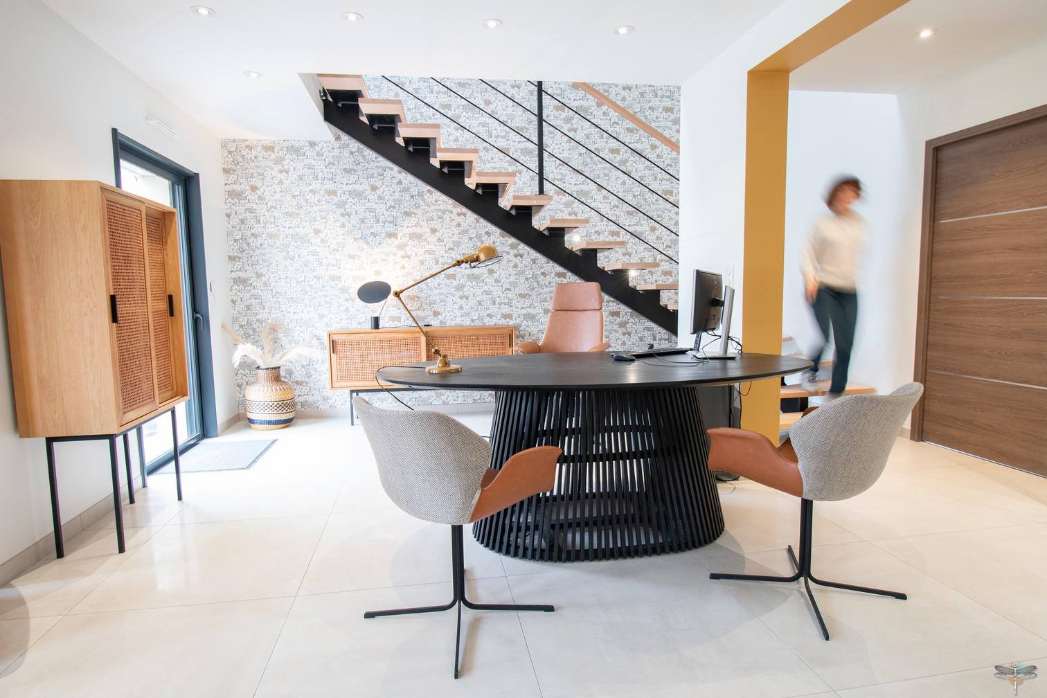 Décoration des bureaux d'une agence de construction de maisons à Compiègne, par Carnets Libellule. Coralie Vasseur est votre architecte d'intérieur UFDI à Compiègne, Annecy et sur toute la France : bureau d'accueil avec escalier métal et bois