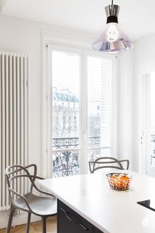 Aménagement et décoration d'une cuisine dans un appartement Haussmannien revisité à l'ambiance design à Paris, par le Studio Coralie Vasseur. Coralie Vasseur est votre architecte d'intérieur et décoratrice UFDI à Annecy, Genève et en Haute Savoie : focus sur les chaises hautes Masters Kartell et l'ampoule de la même forme