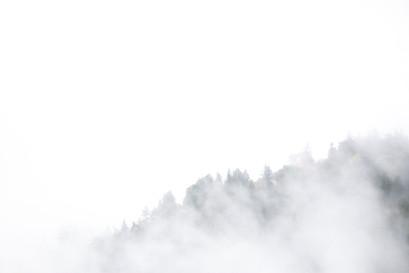 Paysage de montagne qui se dessine derrière les nuages, horizon en noir et blanc