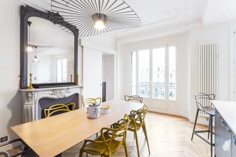 Aménagement et décoration d'une cuisine dans un appartement Haussmannien revisité à l'ambiance design à Paris, par le Studio Coralie Vasseur. Coralie Vasseur est votre architecte d'intérieur et décoratrice UFDI à Annecy, Genève et en Haute Savoie : vue d'ensemble sur la salle à manger et sa vertigo devant la cheminée d'époque