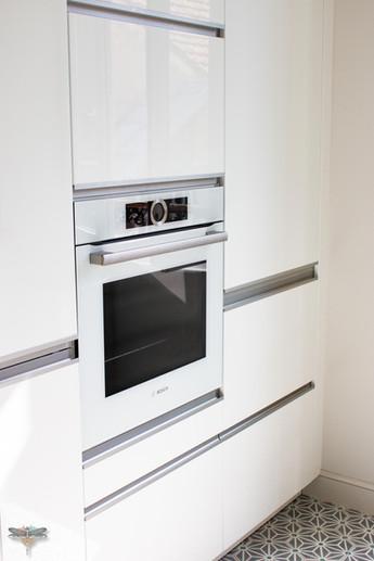 Agencement et décoration d'une cuisine moderne à Senlis dans l'Oise par Carnets Libellule. Coralie Vasseur est votre Décoratrice d'intérieur UFDI à Compiegne : colonnes de cuisine blanc laqué et poignées inox