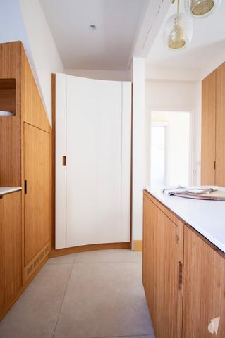 Création d'une cuisine au design sur-mesure à Annecy, par le Studio Coralie Vasseur. Coralie Vasseur est votre architecte d'intérieur et décoratrice UFDI à Annecy, Megève et en Haute Savoie : garde-manger caché derrière une grande porte courbe en acier, ambiance japandi
