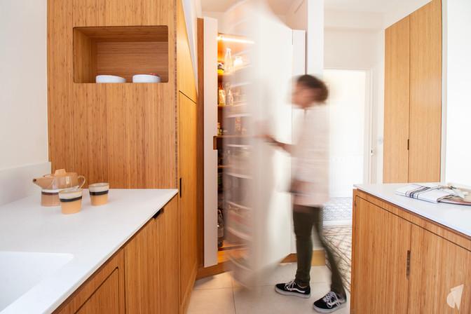 Création d'une cuisine au design sur-mesure à Annecy, par le Studio Coralie Vasseur. Coralie Vasseur est votre architecte d'intérieur et décoratrice UFDI à Annecy, Megève et en Haute Savoie : porte dissimulée dans la cuisine en bambou, ouvrant sur le garde manger.