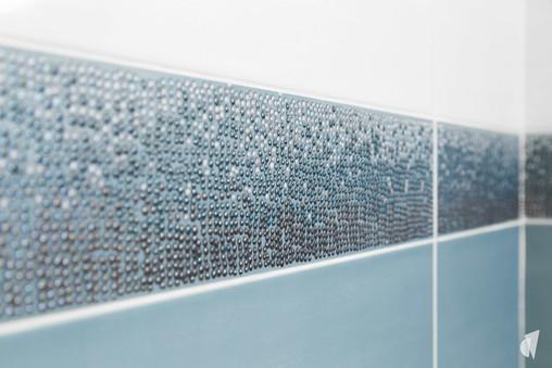 Création d'une salle de bains dans un appartement à Annecy, par le Studio Coralie Vasseur. Coralie Vasseur est votre architecte d'intérieur et décoratrice UFDI à Annecy, Genève et en Haute Savoie : zoom sur le listel 3D bleu et inox