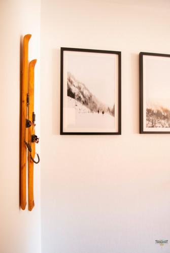 Décoration d'un chalet de montagne à Val d'Isère, par Carnets Libellule. Coralie Vasseur est votre architecte d'intérieur UFDI en Savoie et sur toute la France : zoom sur la décoration murale avec skis en bois et photos de montagne en noir et blanc