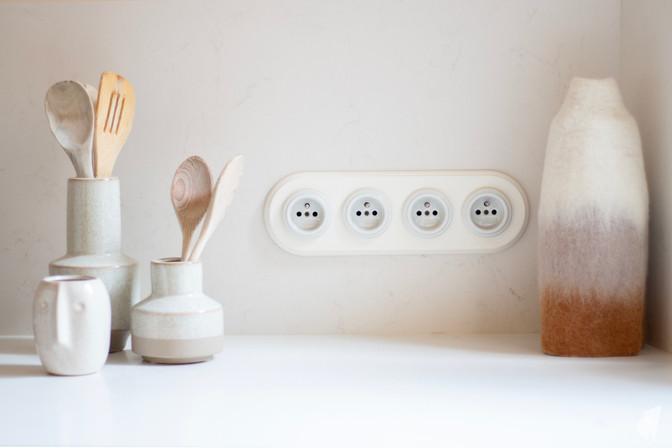 Création d'une cuisine au design sur-mesure à Annecy, par le Studio Coralie Vasseur. Coralie Vasseur est votre architecte d'intérieur et décoratrice UFDI à Annecy, Megève et en Haute Savoie : détail sur les prises en porcelaine et le plan de travail en quartz