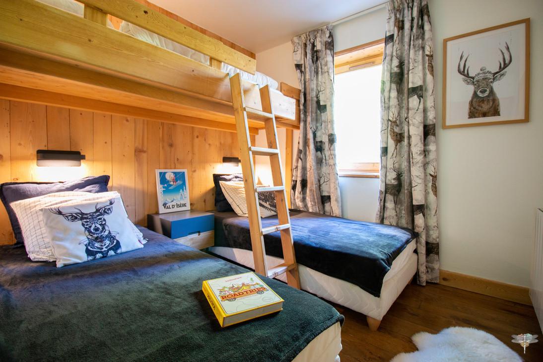 Décoration d'un chalet de montagne à Val d'Isère, par Carnets Libellule. Coralie Vasseur est votre architecte d'intérieur UFDI en Savoie et sur toute la France : vue d'ensemble sur la chambre des enfants, avec lit superposé et rideaux sur-mesure