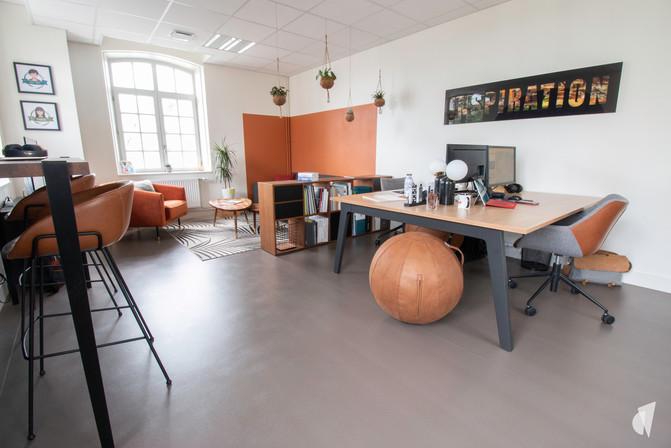 Aménagement et décoration des bureaux d'une startup à Senlis, par l'agence Coralie Vasseur. Coralie Vasseur est votre architecte d'intérieur et décoratrice UFDI à Annecy, Genève et en Haute Savoie : vue d'ensemble sur l'espace flex office et son grand bureau bench