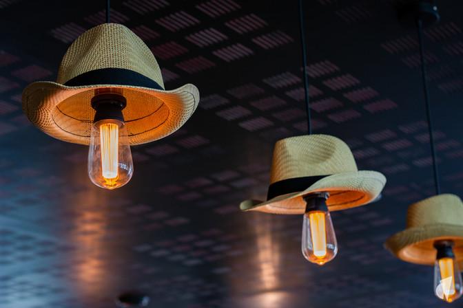 Aménagement et décoration d'un bar restaurant industriel jungle à Compiègne, par l'agence Coralie Vasseur. Coralie Vasseur est votre architecte d'intérieur et décoratrice UFDI à Annecy, Genève et en Haute Savoie : suspensions en chapeau panama diy