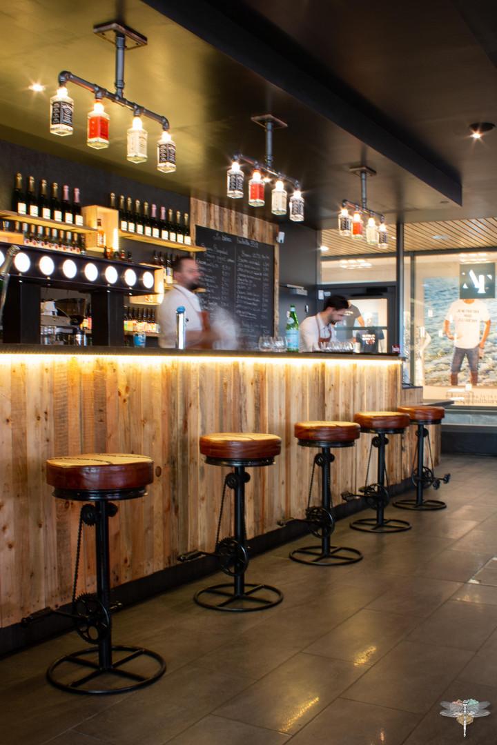 Agencement et décoration du restaurant industriel voyage EAP's CAFE par Carnets Libellule. Coralie Vasseur est votre Décoratrice d'intérieur UFDI à Compiegne : bar indus en bois et métal avec suspensions en bouteilles recyclées