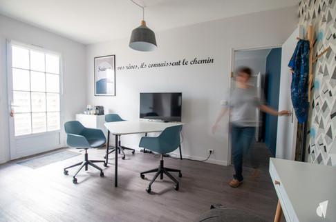 Rénovation et décoration d'une agence de recrutement et coaching à Chantilly, par l'agence Coralie Vasseur. Coralie Vasseur est votre architecte d'intérieur et décoratrice UFDI à Annecy, Genève et en Haute Savoie : vue d'ensemble sur le grand bureau et sa table de réunion, sticker citation au mur