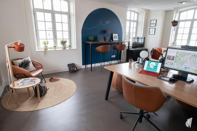 Aménagement et décoration des bureaux d'une startup à Senlis, par l'agence Coralie Vasseur. Coralie Vasseur est votre architecte d'intérieur et décoratrice UFDI à Annecy, Genève et en Haute Savoie : vue d'ensemble sur l'espace flex office avec bureau bench, color zoning, bureau assis debout