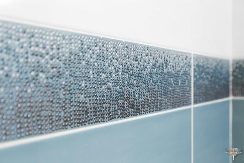 Rénovation et décoration d'une salle de bains parentale lumineuse à Paris par Carnets Libellule. Coralie Vasseur est votre Décoratrice d'intérieur UFDI à Compiegne : détail de la faïence et de son listel en relief