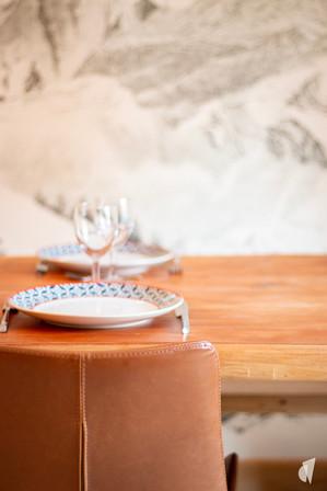Aménagement et décoration d'une agence de construction de maisons à Compiègne, par l'agence Coralie Vasseur. Coralie Vasseur est votre architecte d'intérieur et décoratrice UFDI à Annecy, Genève et en Haute Savoie : zoom sur le cuir des chaises avec le papier peint panoramique en arrière plan