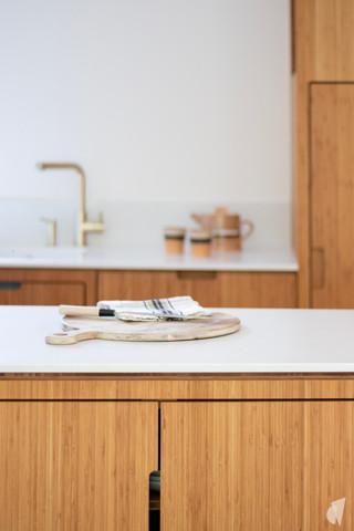 Création d'une cuisine au design sur-mesure à Annecy, par le Studio Coralie Vasseur. Coralie Vasseur est votre architecte d'intérieur et décoratrice UFDI à Annecy, Megève et en Haute Savoie : détail de la cuisine en bambou et quartz avec robinet en laiton